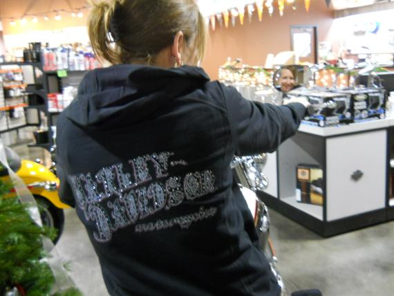 Woman holding a mirror wearing a H-D hoodie